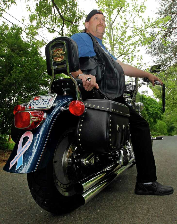 """In this May 3, 2012 photo, breast cancer survivor Robert Kaitz sits on his motorcycle, which displays a male breast cancer survivor ribbon, in Severna Park, Md. Kaitz thought a small growth under his left nipple was just a harmless cyst. By the time he had it checked out in 2006, almost two years later, the lump had started to hurt. The diagnosis of breast cancer was a shock. """"I had no idea in the world that men could even get breast cancer,"""" Kaitz said. Now Kaitz does frequent self-exams and has mammograms every year. The American Cancer Society estimates 1 in 1,000 men will get breast cancer, versus 1 in 8 women. Photo: AP"""