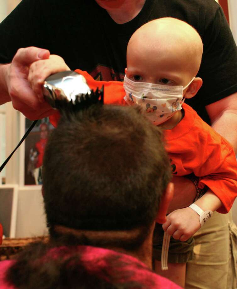 """Preston Winslow, 2, of Houston, who is receiving cancer treatments at Texas Children's Hospital, shaves the head of Danny Cruz, of the Houston Dynamo soccer team, as he and his teammates had their heads shaved by cancer patients at the Texas Children's Cancer Center to benefit and raise awareness for the Dynamo's Craig Waibel's Warriors Bald is Beautiful fundraising event  Wednesday, May 26, 2010, in Houston. This is the second year for the Bald is Beautiful campaign. Last year, """"Waibel's Warriors"""" raised over $40,000 with. all proceeds benefiting Nick's Team and the Curing Childhood Cancer Fund charity supporting cancer research. The team will sport their new looks this Saturday when they play the Philadelphia Union.  ( Johnny Hanson / Chronicle ) Photo: Johnny Hanson / Houston Chronicle"""