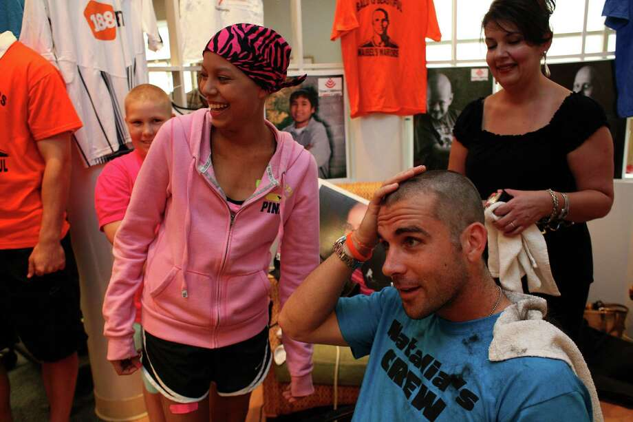 """Michael Chabala, of the Houston Dynamo soccer team, checks his head after Devin Duncan (left), 17, of Houston, who is receiving cancer treatments at Texas Children's Hospital, shaved off Chabala's hair as Chabala and his teammates had their heads shaved by cancer patients at the Texas Children's Cancer Center to benefit and raise awareness for the Dynamo's Craig Waibel's Warriors Bald is Beautiful fundraising event  Wednesday, May 26, 2010, in Houston. """"I haven't shaved it since I did this last year,"""" Chabala said of getting his hair cut. """"We want to let them know they are not alone and support them."""" This is the second year for the Bald is Beautiful campaign. Last year, """"Waibel's Warriors"""" raised over $40,000 with. all proceeds benefiting Nick's Team and the Curing Childhood Cancer Fund charity supporting cancer research. The team will sport their new looks this Saturday when they play the Philadelphia Union.  ( Johnny Hanson / Chronicle ) Photo: Johnny Hanson / Houston Chronicle"""