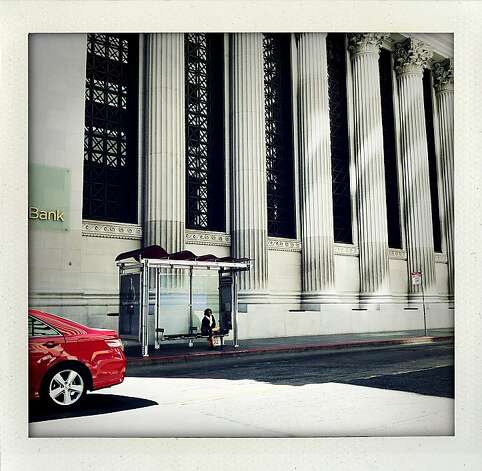 """Bank Stop"" - A woman waits at the bus stop under a columned bank building as a shiny red car drives by on Montgomery Street at California Street. Photo: Meghan Gerzon Rand"