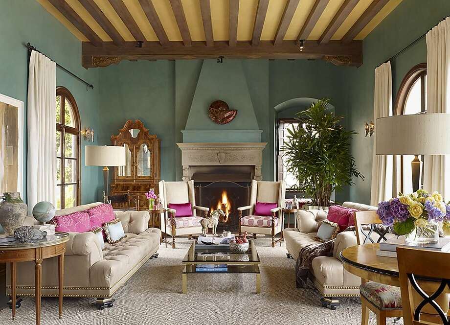 The living room with its fireplace and high ceilings leads to the large balcony via the arched French doors, contributing to the property's sense of openness. Photo: Jennifer Salyers