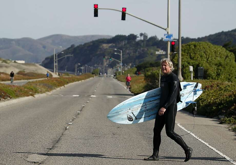 Mark Massara walks across the Great Highway from his home to surf the waves at Ocean Beach in San Francisco, Calif. on Saturday, April 7, 2012. Photo: Paul Chinn, The Chronicle