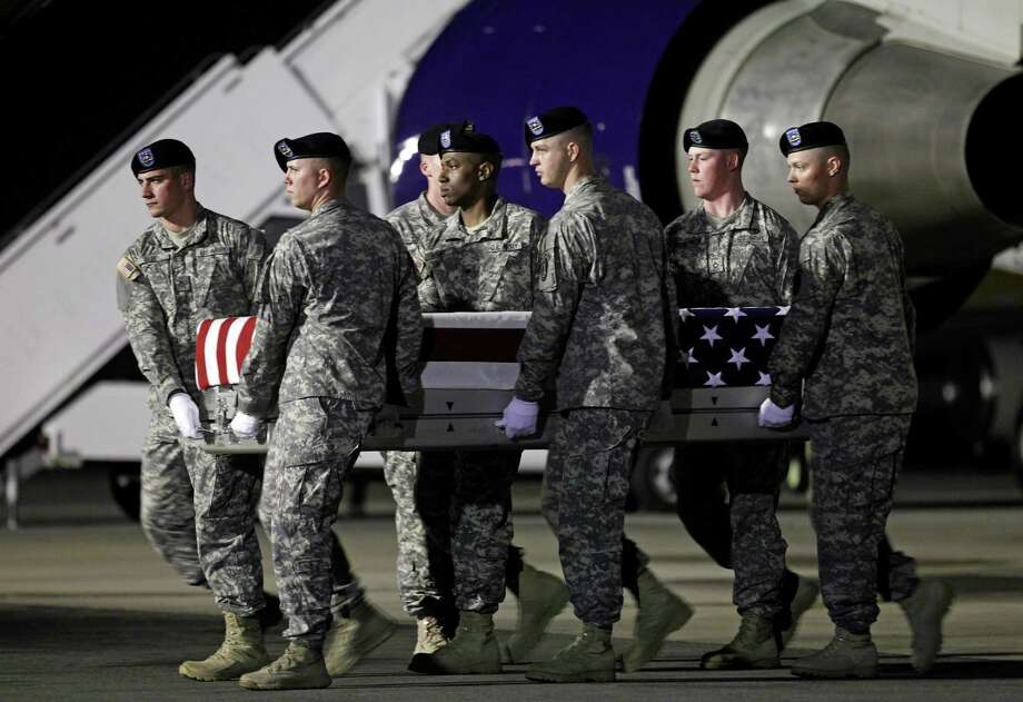An Army team at Dover Air Force Base, Del., carries the remains of Capt. Bruce Clark on Thursday. The Pentagon has not release details of his death. Photo: Jose Luis Magana / FR159526 AP