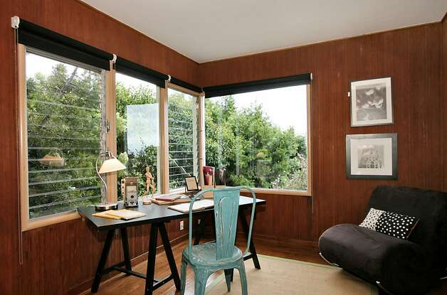 Wood paneling and a wall of windows accentuate the home s office area. Photo: Liz Rusby