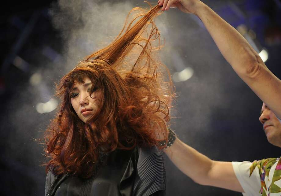 I'd like to introduce you to something I call a 'comb': A hair stylist tames a model's unruly tresses on stage at the China Beauty Expo in Shanghai. 