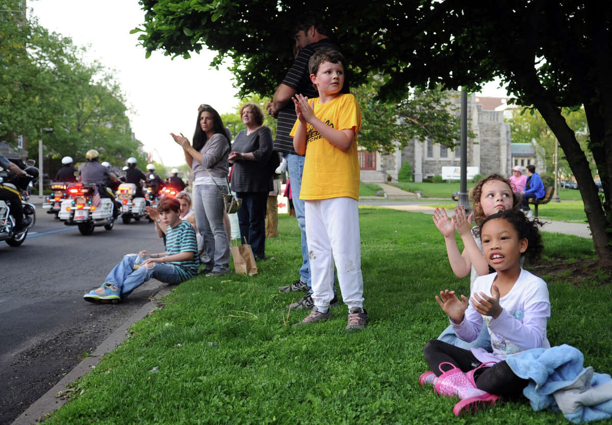 Leilani Nguyen, far right, and Lila Parkel, 5, right, clap during the 6th annual Stamford Police Department Memorial Parade on Friday, May 4, 2012.