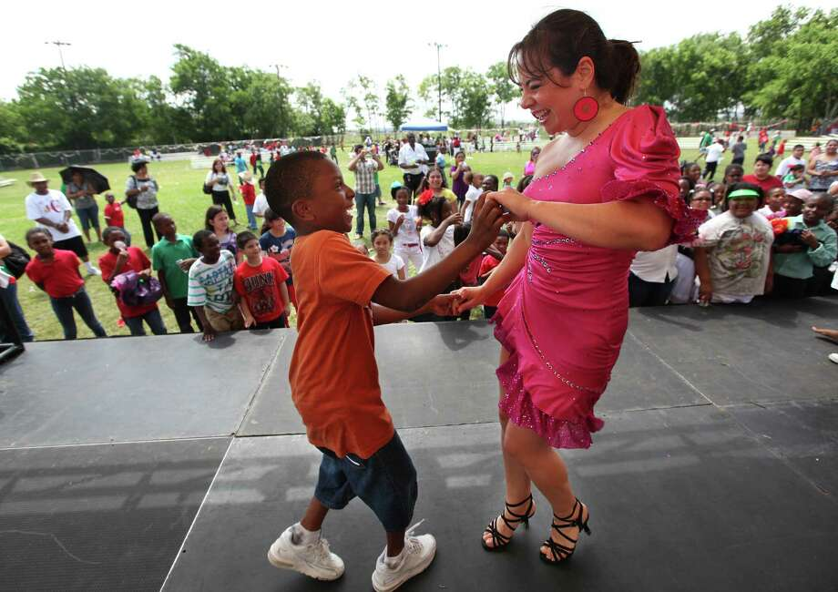 Marque Nelson, 9, dances with Maria Fernanda Kelley during La Compania de Danza Cafe's salsa performance at The Varnett Public School southwest campus on Thursday, May 4, 2012, in Houston. Photo: Mayra Beltran, Houston Chronicle / © 2012 Houston Chronicle