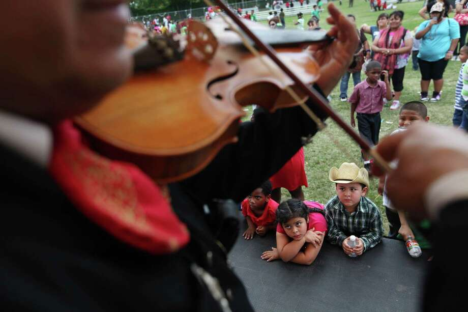 Wendy Netro and brother Brayan Netro listen to Mariachi Santa Cecilia at The Varnett Public School southwest campus on Thursday, May 4, 2012, in Houston. Photo: Mayra Beltran, Houston Chronicle / © 2012 Houston Chronicle