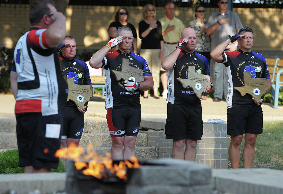 "Members of the Texas Law Enforcement Officers Memorial Bike Trek team salute and honor local area fallen officers at the San Antonio Police Department Training Academy on Friday, May 4, 2012. The five officers joined other law enforcement agencies in the ""We Remember"" Memorial bicycling trek across Texas which spanned over 1,000 miles in Texas. The ride which consisted of about 24 cyclists stopped at the Training Academy to honor four area officers killed in 2011. The four officers holding the memorial plaques are: Dayton Neff of Odessa Police Department (from left), Chaplain Paul Worley of SAPD, Dave Smith of SAPD and Steve Beilstein of SAPD. The four fallen officers honored were: Bexar County Sheriffs Department's Sgt. Kenneth Vann, San Diego Police Department's Jeremy Henwood who grew up in San Antonio, SAPD officer Stephanie Brown and Bexar County Constable's Office Sgt. Mark Scianna. This is the fifth year that law enforcement officers have participated in the memorial ride. Kin Man Hui/Express-News. Photo: KIN MAN HUI, SAN ANTONIO EXPRESS-NEWS / ©2012 San Antonio Express-News"