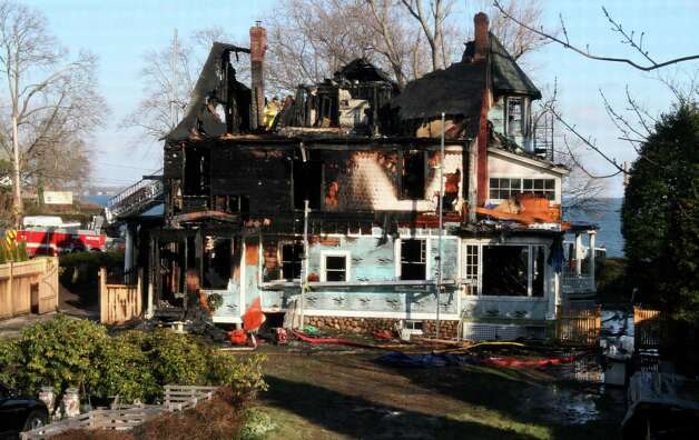 In this Dec. 25, 2011, file photo, firefighters investigate a house in Stamford where a fire left five people dead. An attorney for Matthew Badger, father of three girls killed in the fire, said an intent to sue the city of Stamford was filed Friday, May 4, 2012, for allowing the house to become a fire trap by failing to properly oversee construction. A contractor had been renovating the house at the time of the fire.  (AP Photo/Tina Fineberg, File) Photo: Tina Fineberg, Associated Press / AP2011