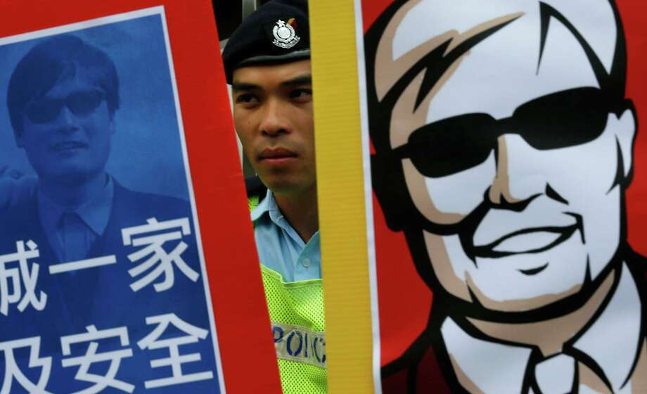 "A police officer stands guard in the middle of two images featuring blind Chinese activist Chen Guangcheng during a protest in front of the Chinese central government's liaison in Hong Kong Friday, May 4, 2012. Chen at the center of a diplomatic standoff between the United States and China said Friday his situation is ""dangerous,"" and that American officials have been blocked from seeing him for two days and friends who have tried to visit have been beaten up. (AP Photo/Vincent Yu) Photo: Vincent Yu / AP"