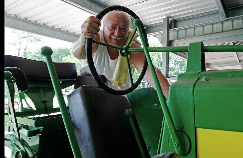 Larry Steed, president of  Pearland Bluebonnet  Antique Tractor Club, can't resist climbing onto one of his John Deere tractors. Photo: James Nielsen / © Houston Chronicle 2012