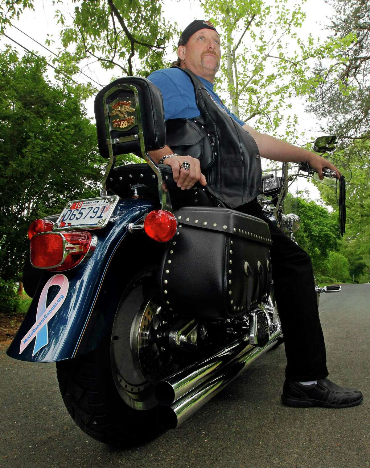 In this May 3, 2012 photo, breast cancer survivor Robert Kaitz sits on his motorcycle, which displays a male breast cancer survivor ribbon, in Severna Park, Md. Kaitz thought a small growth under his left nipple was just a harmless cyst. By the time he had it checked out in 2006, almost two years later, the lump had started to hurt. The diagnosis of breast cancer was a shock.