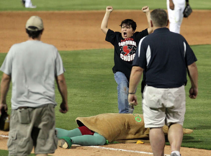 A young fan rejoices after tackling the Henry's Puffy Taco mascot during a break in the action at the Missions versus Frisco Roughriders game at Wolff Stadium on Friday, May 4, 2012.