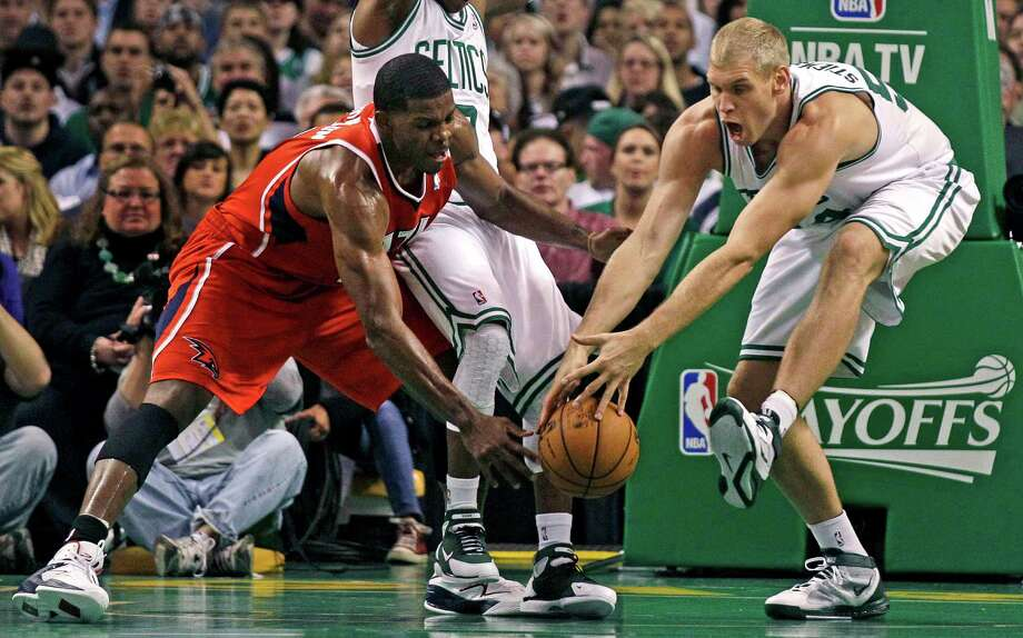 The Celtics' Greg Stiemsma, right, and Hawks guard Joe Johnson show some early energy in a game that went into overtime before Boston eked out a win. Photo: Charles Krupa / AP