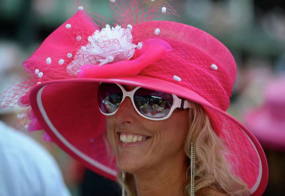 Stephanie Tzouanakis of Louisville, KY enjoys the sun and the racing atmosphere at Churchill Downs in Louisville, KY. on a day when hats are everywhere the day before the 138th running of The Kentucky Derby May 4, 2012.(Skip Dickstein / Times Union) Photo: SKIP DICKSTEIN / 2012