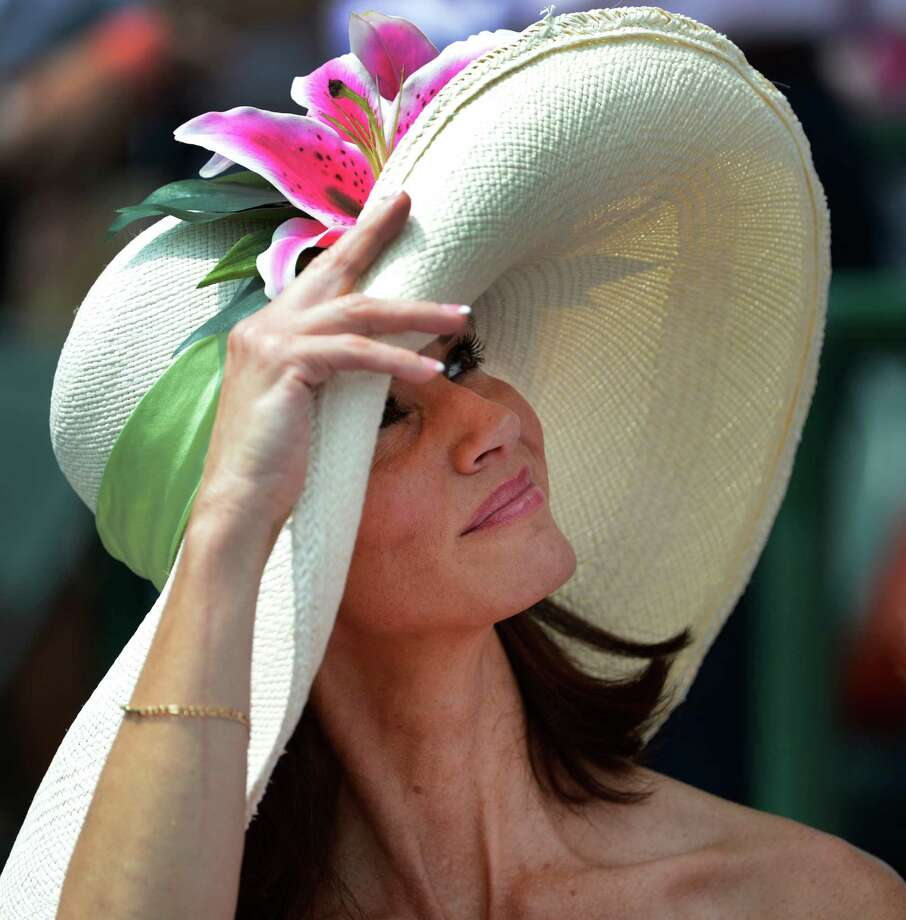 A patron of thoroughbred racing enjoys the sun and the racing atmosphere at Churchill Downs in Louisville, KY. on a day when hats are everywhere the day before the 138th running of The Kentucky Derby May 4, 2012.(Skip Dickstein / Times Union) Photo: SKIP DICKSTEIN / 2012