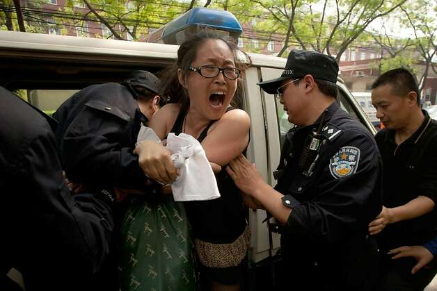 "A protester is removed by police from outside the Chaoyang Hospital in Beijing where Chinese activist Chen Guangcheng is staying, on May 4, 2012. The protester had been holding a banner reading ""Daqing oil management corruption. Forced redundancy, no money to eat. I want to eat, want to live."" AFP PHOTO / Ed JonesEd Jones/AFP/GettyImages Photo: Ed Jones, AFP/Getty Images"