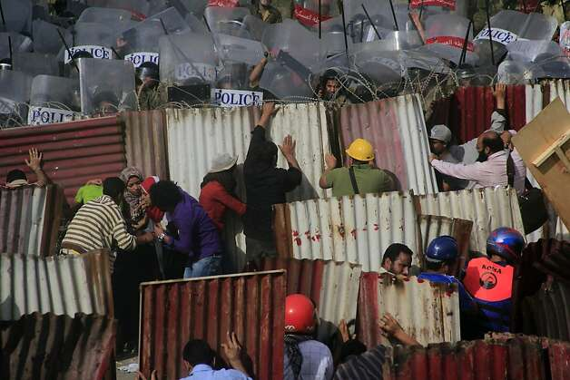 Protesters take shelter during brick throwing clashes outside the Ministry of Defense in Cairo, Egypt, Friday, May 4, 2012. Egyptian armed forces and protesters clashed in Cairo on Friday, with troops firing water cannons and tear gas at demonstrators who threw stones as they tried to march on the Defense Ministry, a flashpoint for a new cycle of violence only weeks ahead of presidential elections. (AP photo/Hamada Elrasam) Photo: Hamada Elrasam, Associated Press