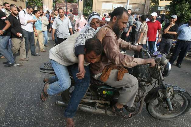 Injured protesters are evacuated by motorbike in Cairo, Egypt, Friday, May 4, 2012. Egyptian armed forces and protesters clashed in Cairo on Friday, with troops firing water cannons and tear gas at demonstrators who threw stones as they tried to march on the Defense Ministry, a flashpoint for a new cycle of violence only weeks ahead of presidential elections.(AP Photo/Mohammed Abu Zaid) Photo: Mohammed Abu Zaid, Associated Press