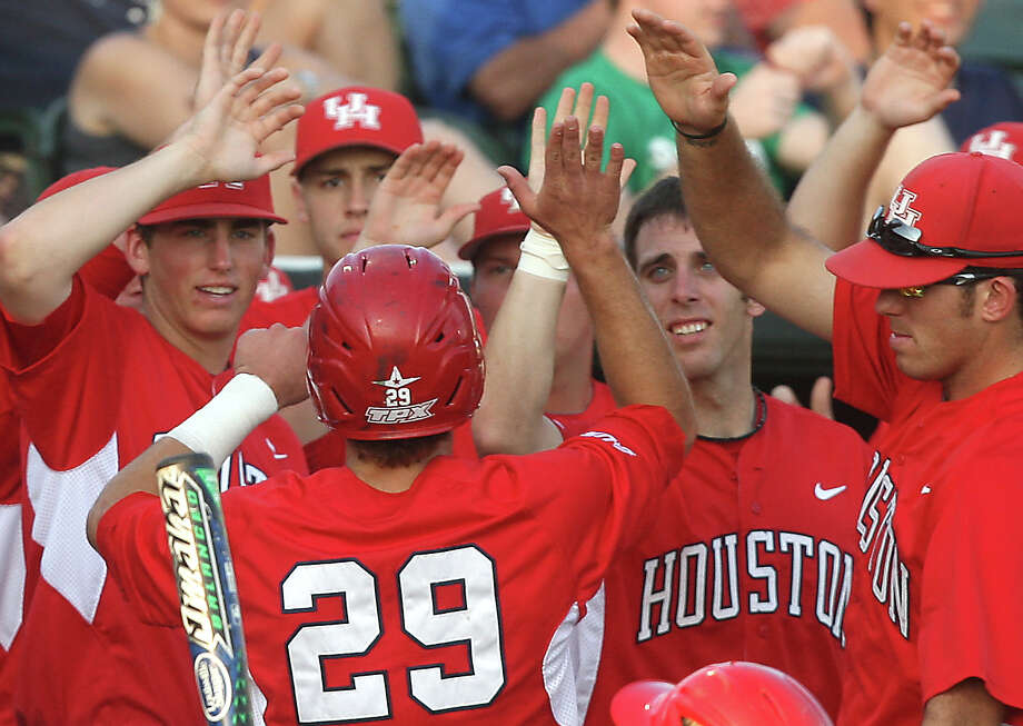 University of Houston center fielder Zack Gibson (29) is congratulated by teammates Logan Piper (left), John Cannon (right center), and Mo Wiley (far right) after scoring during the second inning against Rice at Reckling Park on Friday, May 4, 2012 in Houston, Texas. Photo: J. Patric Schneider, For The Chronicle / Houston Chronicle