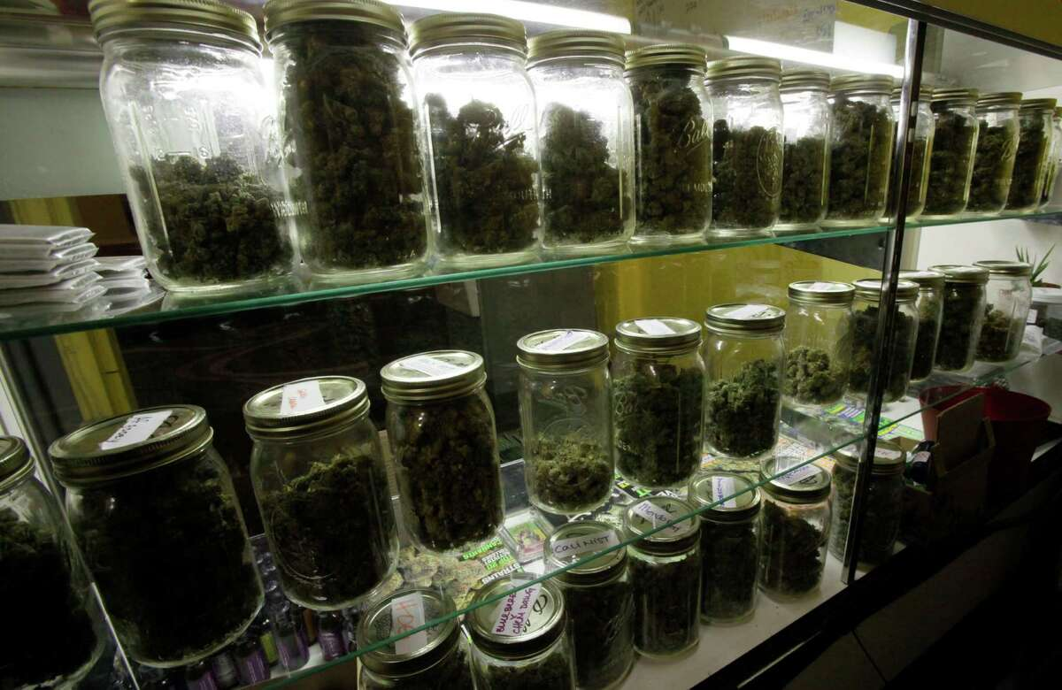 Traditional canning jars hold varieties of marijuana in a cabinet at the La Brea Collective medical marijuana dispensary in Los Angeles Tuesday, Nov. 17, 2009. Los Angeles County's district attorney says he intends to prosecute owners of marijuana dispensaries that take cash for pot. (AP Photo/Reed Saxon)