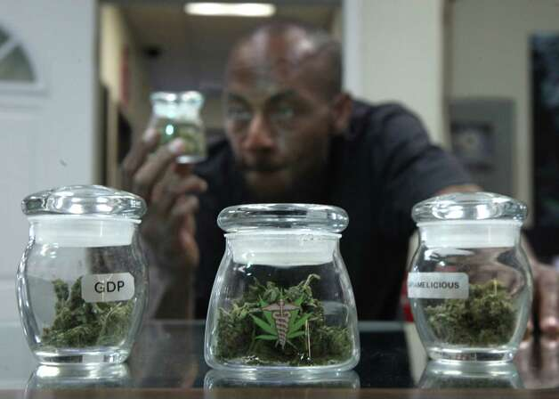 Medical marijuana patient Ezekiel Muses, who uses the drug for back pain, checks out a jar of medical marijuana at the CANNA CARE medical marijuana shop in Sacramento, Calif., Tuesday, Sept. 21, 2010. A coalition of medical marijuana advocates came out Tuesday against a California ballot initiative that would legalize the drug for recreational use and tax its sales. (AP Photo/Rich Pedroncelli) Photo: Rich Pedroncelli, ASSOCIATED PRESS / ASSOCIATED PRESS