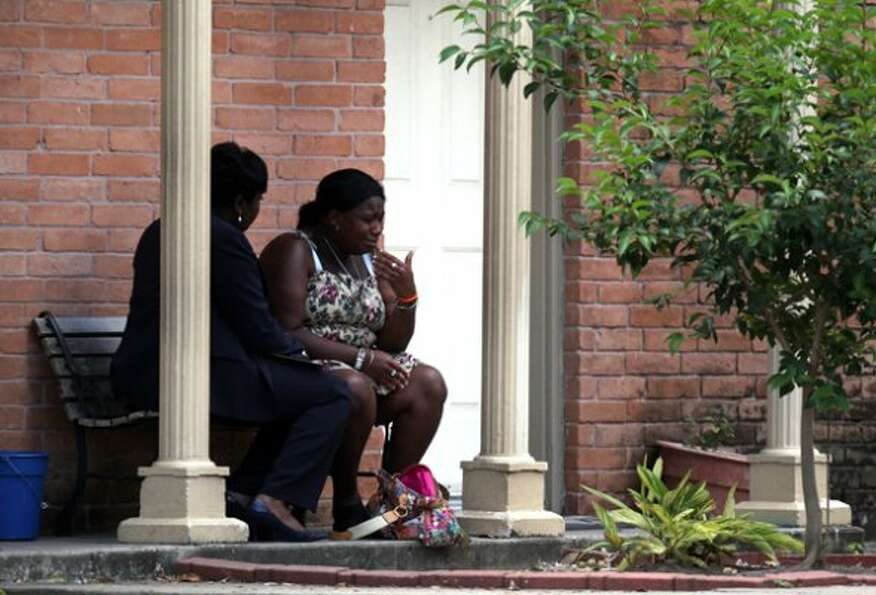 A mother reacts while speaking with HPD Homicide Sgt. Ora Chandler, left, as police investigate the