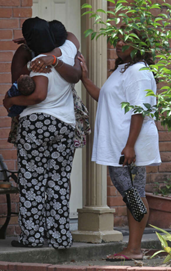 A mother, left, is comforted, as police investigate the death of her near 6-month-old son who was found in the refrigerator by firefighters where he lived with his father at The University Apartments on the 7100 block of Beechnut Wednesday, May 2, 2012, in Houston.  Investigators say the baby's father called 911 this morning, saying he was suicidal. When rescue personnel arrived at the apartment around 7:40 a.m. no one opened the door. Neighbors told firefighters that a baby was in the apartment. Fearing for the child's safety, firefighters broke into the unit and found the father collapsed on the floor. He was incoherent and said he had killed his son, police said. The baby was found wrapped in a blanket, dead in refrigerator. The father, who has not been identified, became violent and had to be subdued. He was taken to a hospital where he remains. ( Johnny Hanson / Houston Chronicle ) Photo: Johnny Hanson, Houston Chronicle / © 2012  Houston Chronicle