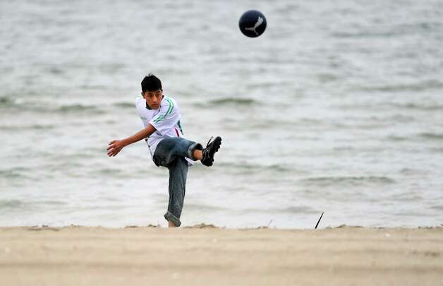 Carlos Munguia plays a game of beach soccer with friends at Seaside Park in Bridgeport Saturday, May 5, 2012. Photo: Autumn Driscoll / Connecticut Post
