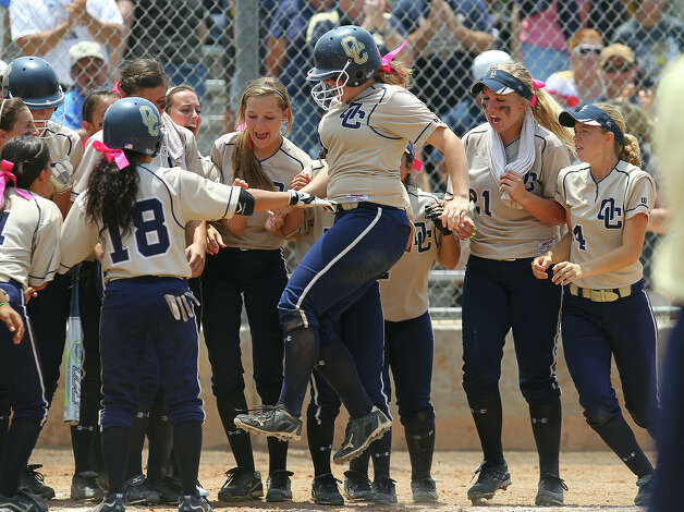 O'Connor's Maegan Taylor (cq) (center) jumps toward home plate as her teammates congratulate her on a two-run homer in the fifth inning against Judson in the second round of Class 5A softball playoffs on Saturday, May 5, 2012. O'Connor took the series by winning the first game on Friday and then again on Saturday with a 10-3 win over Judson. Photo: KIN MAN HUI, Kin Man Hui/Express-News / ©2012 San Antonio Express-News