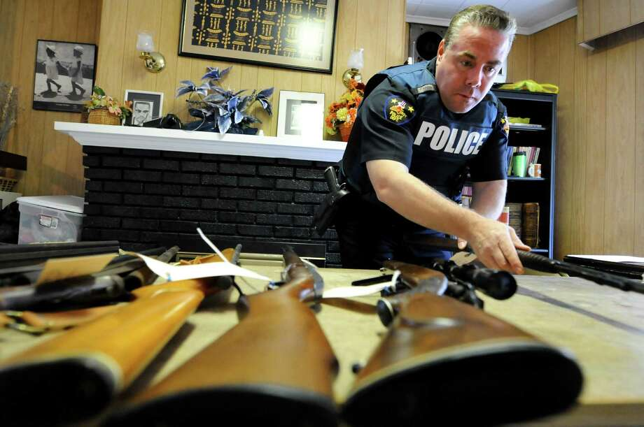 Troy Police Officer Kevin Sessions tags a rifle with its make, model and serial number during a gun buy-back program on Saturday, May 5, 2012, at Bethel Baptist Church in Troy, N.Y. The initiative, conducted in collaboration with the Troy Police Department and Rensselaer County District Attorney?s Office, is designed to remove lethal weapons from the streets. (Cindy Schultz / Times Union) Photo: Cindy Schultz / 00017583A