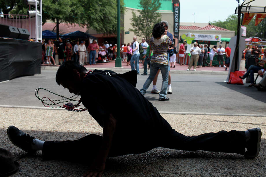 "Johnny Ray Morales, who says he loves to dance and can do splits although his legs are severely disabled, does a split as ""Federales del Norte"" performs during the Cinco de Mayo celebration at Market Square in San Antonio on Saturday, May 5, 2012. Photo: Lisa Krantz, SAN ANTONIO EXPRESS-NEWS / SAN ANTONIO EXPRESS-NEWS"