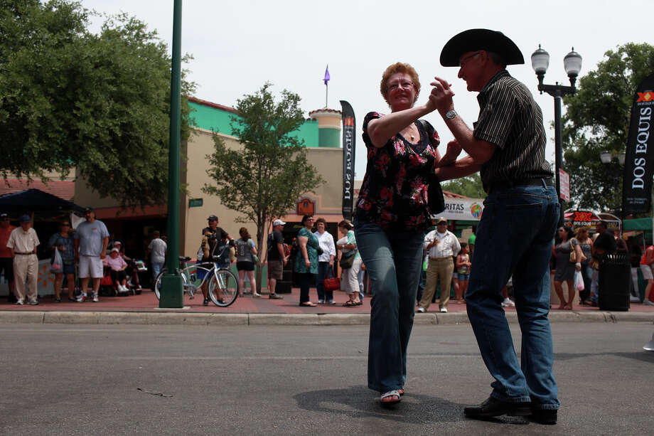 """metro - James and Stephanie Lambert, of Liverpool, England, dance as """"Federales del Norte"""" plays during the Cinco de Mayo celebration at Market Square in San Antonio on Saturday, May 5, 2012. Lisa Krantz/San Antonio Express-News Photo: Lisa Krantz, SAN ANTONIO EXPRESS-NEWS / SAN ANTONIO EXPRESS-NEWS"""