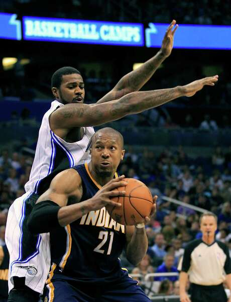The Pacers' David West tries to elude Orlando's Earl Clark on the way to the basket. Photo: AP