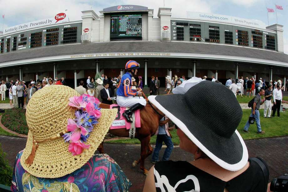 Race goers watch as jockey Colm O'Donoghue rides Revolving through the paddock before the third race at the 138th Kentucky Derby horse race at Churchill Downs Saturday, May 5, 2012, in Louisville, Ky. (AP Photo/Mark Humphrey) Photo: Mark Humphrey, Associated Press / Copyright 2012 The Associated Press. All rights reserved. This material may not be published, broadcast, rewritten or redistribu