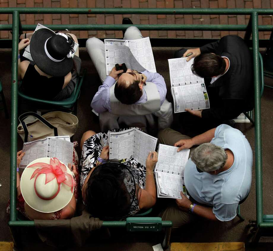 Spectators study their race programs before the 138th Kentucky Derby horse race at Churchill Downs Saturday, May 5, 2012, in Louisville, Ky. (AP Photo/Charlie Riedel) Photo: Charlie Riedel, Associated Press / AP