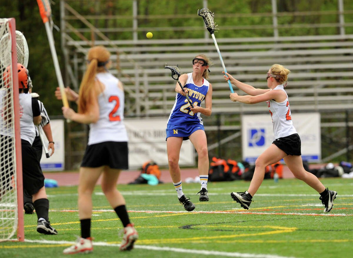 Newtown's Meaghan Brophy shoots and scores on Ridgefield goalie Maggie Philbin while under pressure from Hannah Dighton during their game at Ridgefield High School on Saturday, May 5, 2012. Newtown won 15-14.