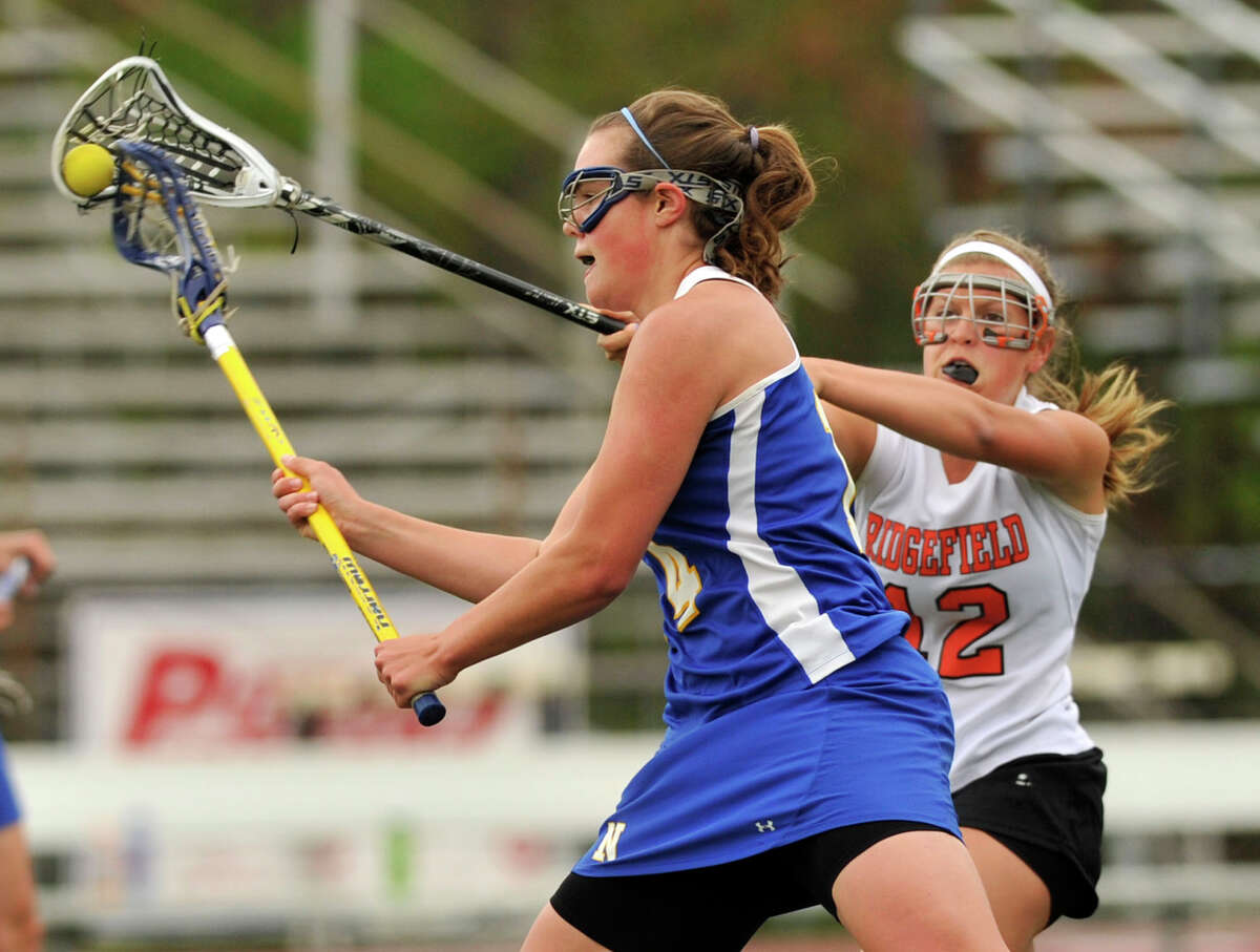 Ridgefield's Melissa Galione, right, blocks the shot of Newtown's Meredith Bridges during their game at Ridgefield High School on Saturday, May 5, 2012. Newtown won 15-14.