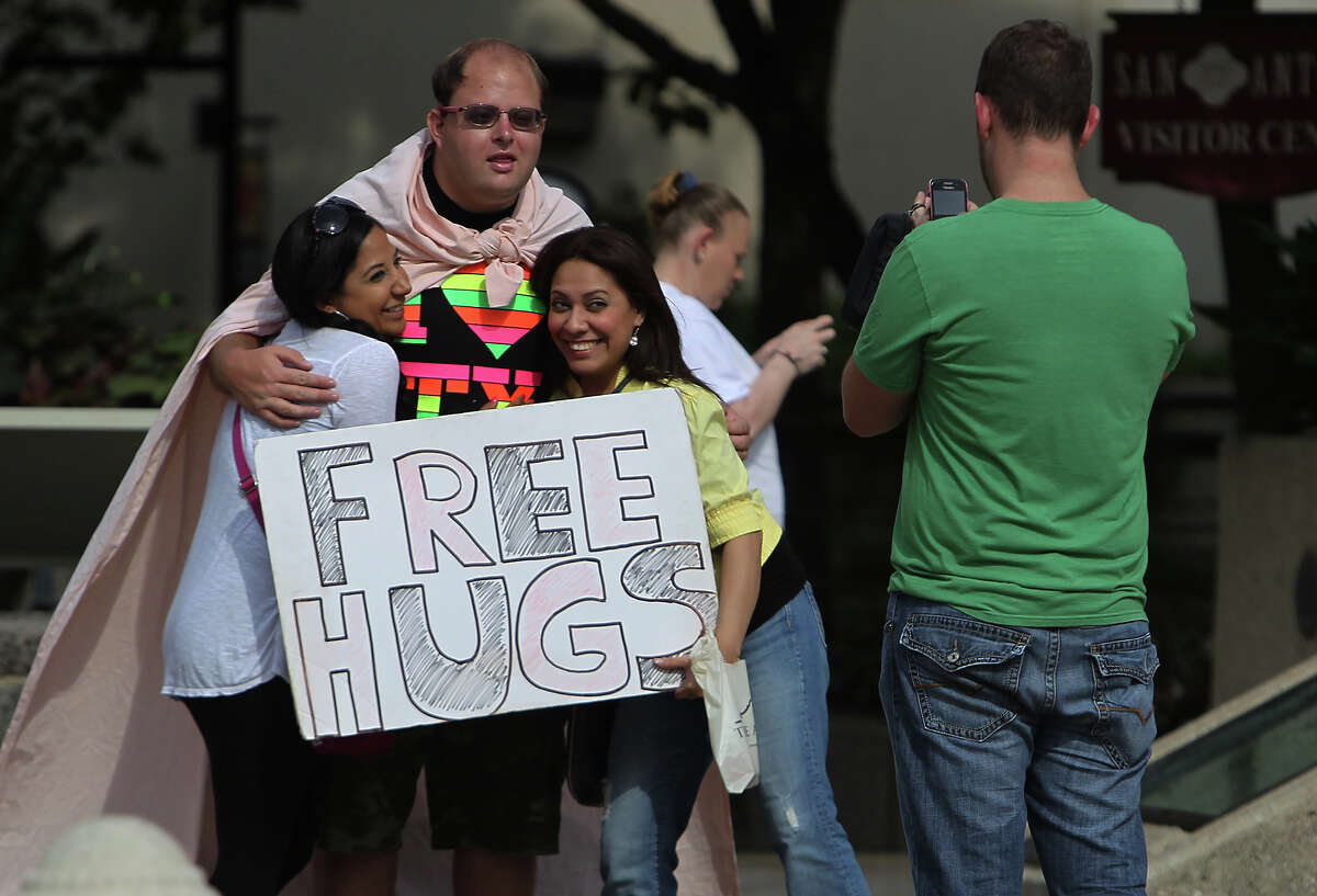 Christopher Webster hugs Laura Reyna (left) and Denise Gongora while their friend Mike Simmons takes their picture near Alamo Plaza this month. Webster offers free hugs there most Saturday mornings.