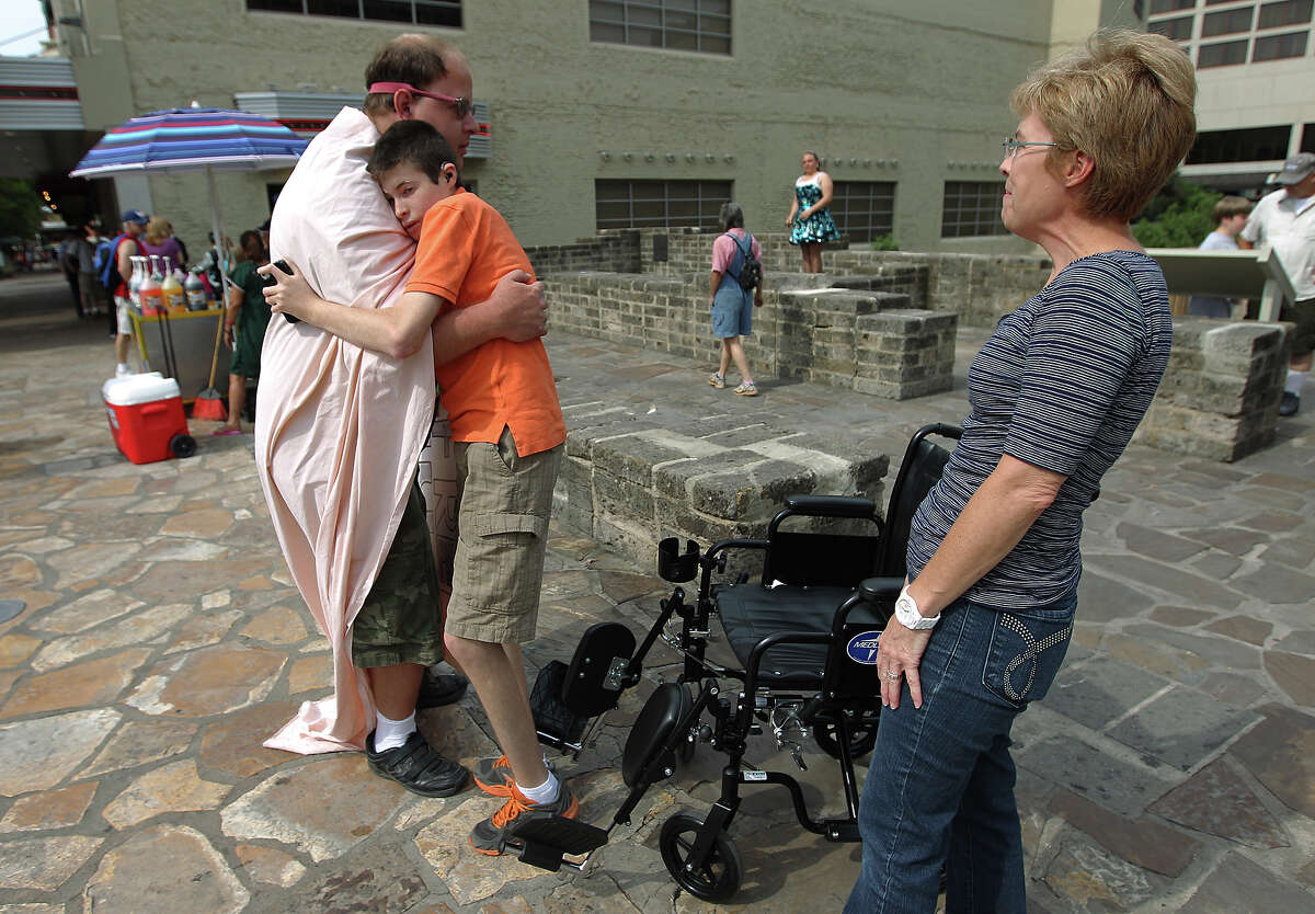 Christopher Webster shares a hug with Kyle Springer as Springer's mother, Karen Springer, watches. Webster has Asperger's syndrome, which causes difficulty interacting with others. Kyle Springer, who uses the wheelchair, has a rare chromosome disorder.