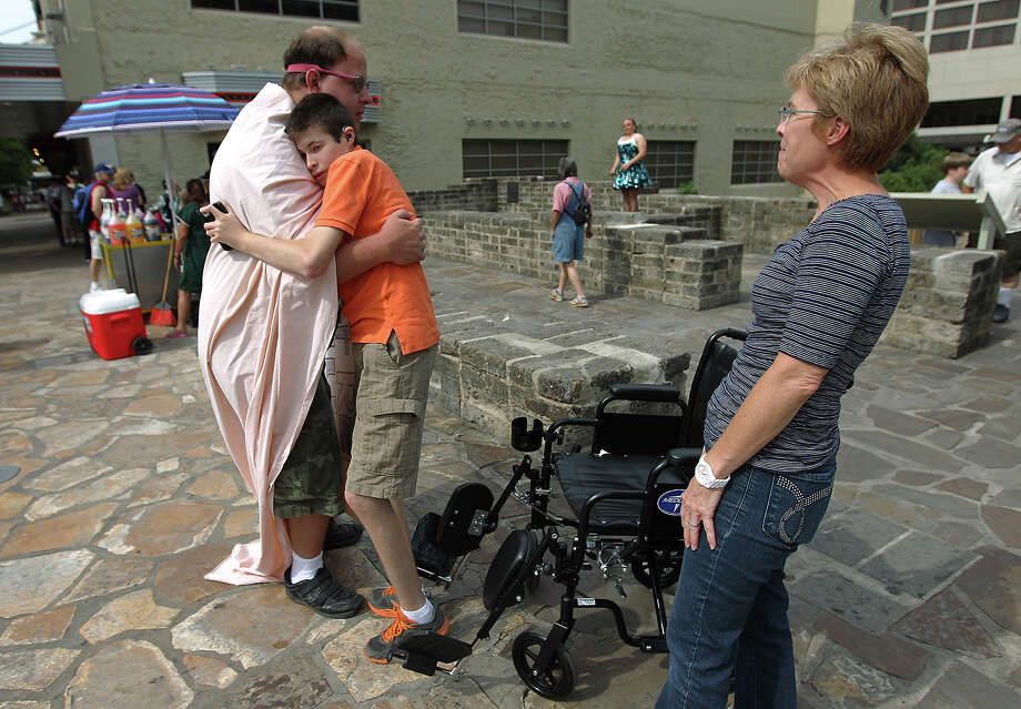 Christopher Webster shares a hug with Kyle Springer as Springer's mother, Karen Springer, watches. Webster has Asperger's syndrome, which causes difficulty interacting with others. Kyle Springer, who uses the wheelchair, has a rare chromosome disorder. Photo: KIN MAN HUI, San Antonio Express-News / ©2012 San Antonio Express-News