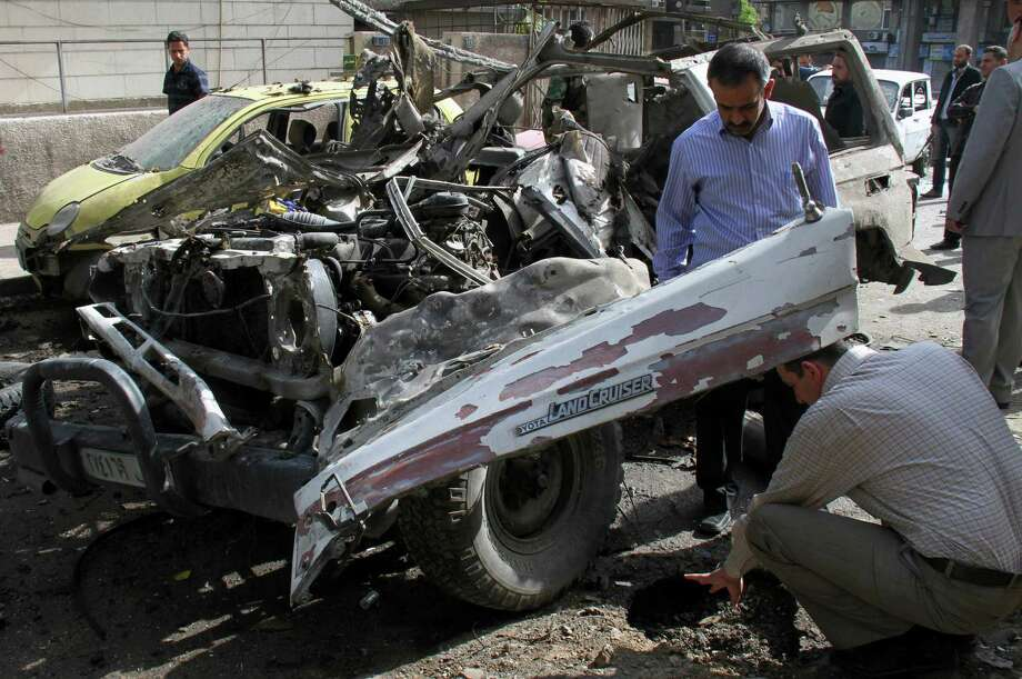 People look at destroyed vehicles after an explosion on al-Thawra Street in Damascus, Syria, on Saturday. According to eyewitnesses, an explosive device was planted underneath a military car  No one was hurt.ba, who was killed by Syrian security forces along with four protesters on Friday, while they were attending the funeral of activist, Odai Junblat, during his funeral procession, in Kfar Suseh area in Damascus, Syria, on Saturday May 5, 2012. (AP Photo) Photo: Bassem Tellawi / AP