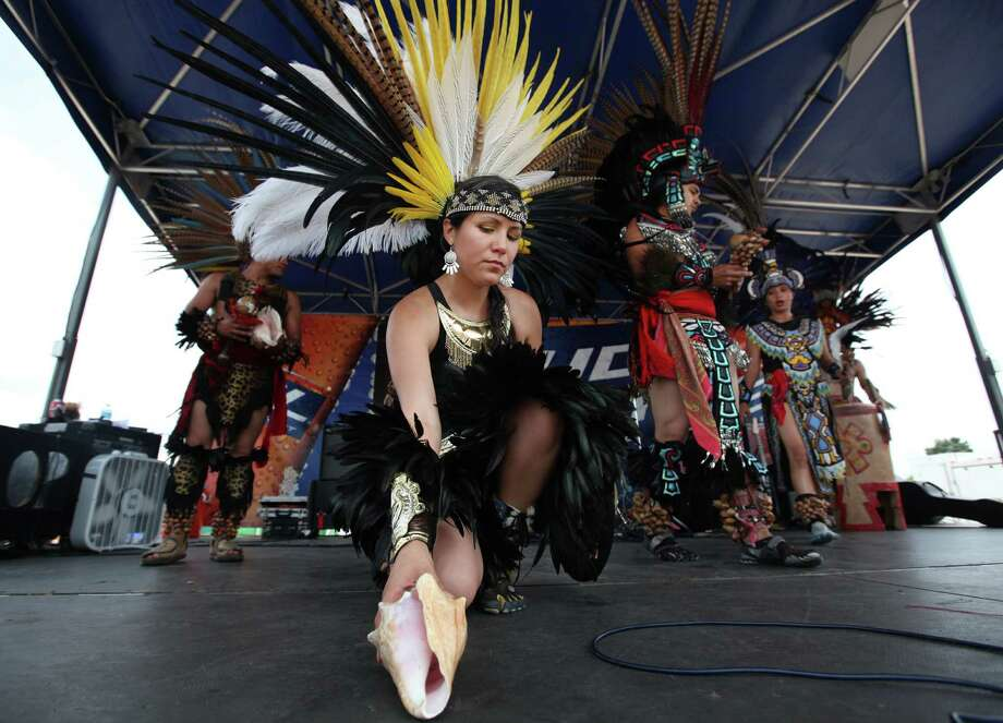 Monica Villareal, of Taxcayolotl Danza Azteca, places down the seashell after ceremony before performing at the East End Street Festival. Photo: Mayra Beltran, Houston Chronicle / © 2012 Houston Chronicle