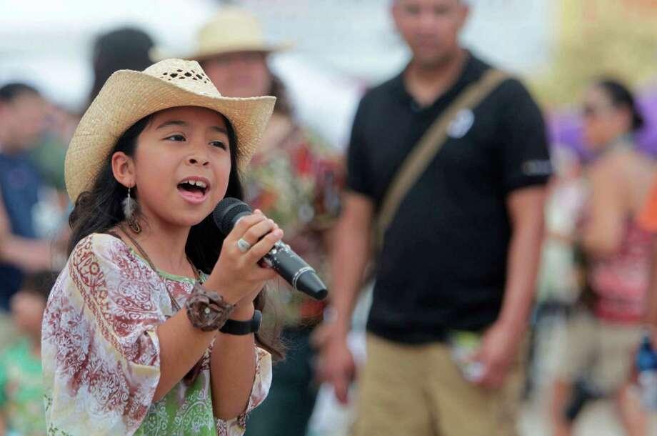 Madalyn Hernandez, 10, sings during the East End Street Festival on Saturday, May 5, 2012, in Houston. Photo: Mayra Beltran, Houston Chronicle / © 2012 Houston Chronicle