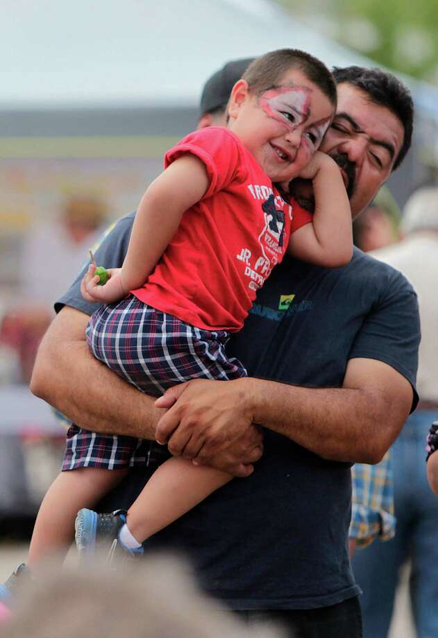 Javier Alcantar carries son Ernesto Alcantar, 2, as they watch the Aztec Dancers perform. Photo: Mayra Beltran, Houston Chronicle / © 2012 Houston Chronicle