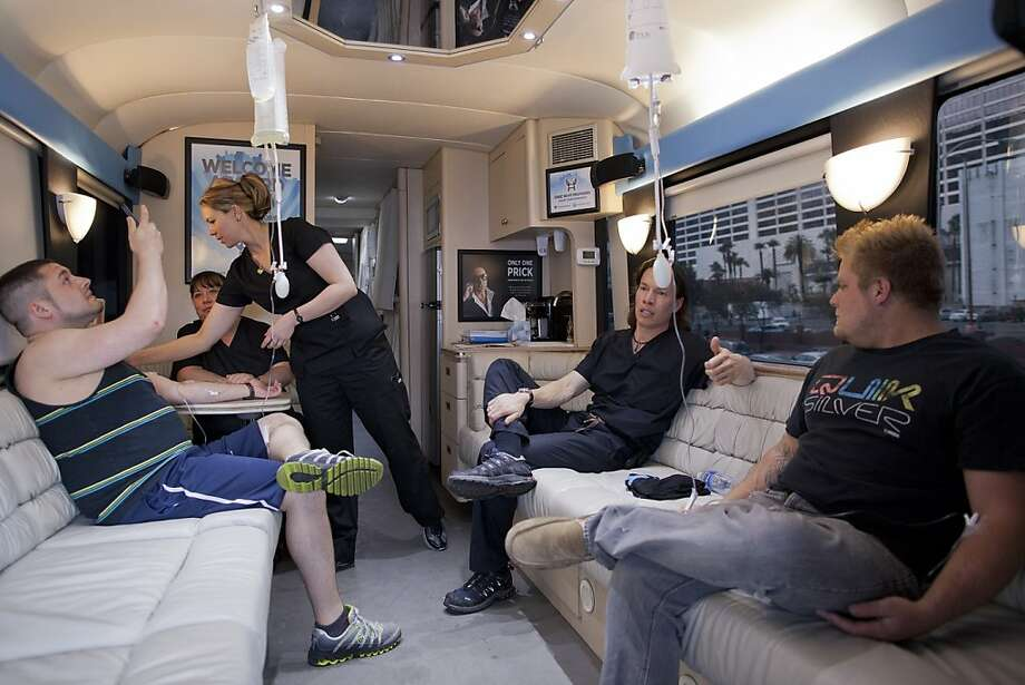 Bryan Dalia, left, of Caldwell, N.J. makes a photo of his IV bag while being treated on the Hangover Heaven bus by EMT Stacey Kreitlow, second from left, and Dr. Jason Burke, second from right, as another patient named Alex, right, looks on, Saturday, April 14, 2012, in Las Vegas.  The bus picked up 16 patients on its first weekend as a mobile treatment center for tourists who spent the night before drinking in all the nightlife Las Vegas has to offer. For a fee, they get a quick morning-after way to rehydrate, rejuvenate and resume their revelry. (AP Photo/Julie Jacobson) Photo: Julie Jacobson, Associated Press