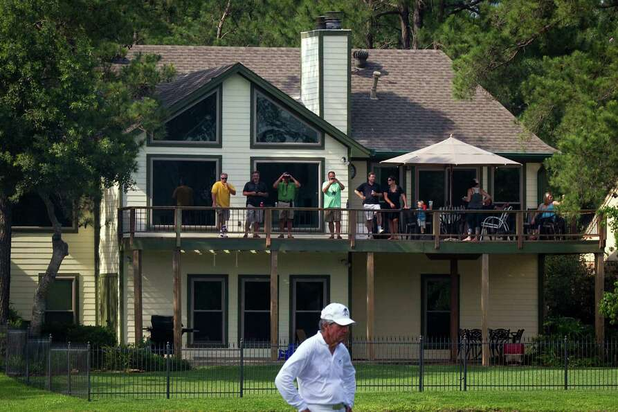 Fans watch from a balcony as Gary Player lines up a putt during The Insperity Championship Greats of