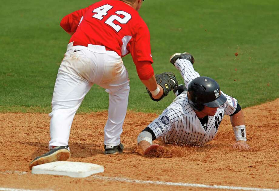 Rice University's Michael Ratterree right, is tagged out at first base by the University of Houston's Jacob Lueneburg during the fourth inning of college baseball game action at Reckling Park Saturday, May 5, 2012, in Houston. Photo: James Nielsen, Chronicle / © Houston Chronicle 2012