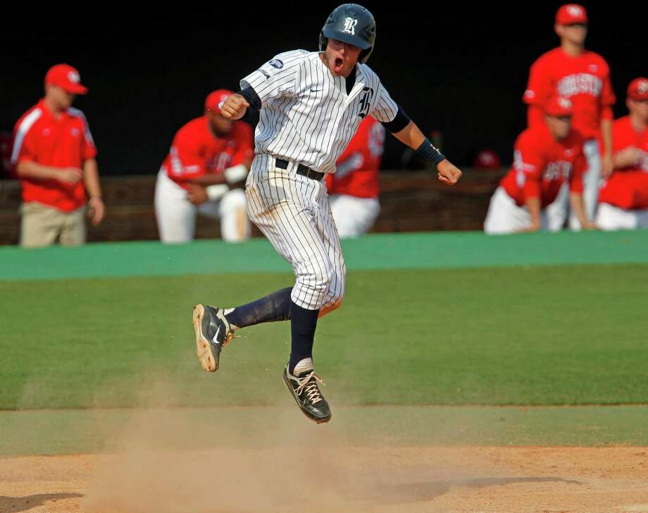 Rice University's Christian Stringer jumps in the air after scoring the winning run against the University of Houston during the tenth inning of college baseball game action at Reckling Park Saturday, May 5, 2012, in Houston. Photo: James Nielsen, Chronicle / © Houston Chronicle 2012